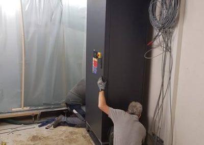 Die ersten Kühlgeräte werden eingebaut. Diese werden durch die Kältezentrale versorgt und geben die Kälte an die Raumluft ab.  Während des Einbaus muss die heikle EDV geschützt werden (Hintergrund).